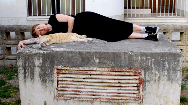 woman in black laying together with yellow tabby cat in street