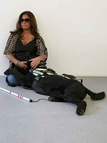 visually impaired woman with glasses sitting on floor with black labradoodle guide dog