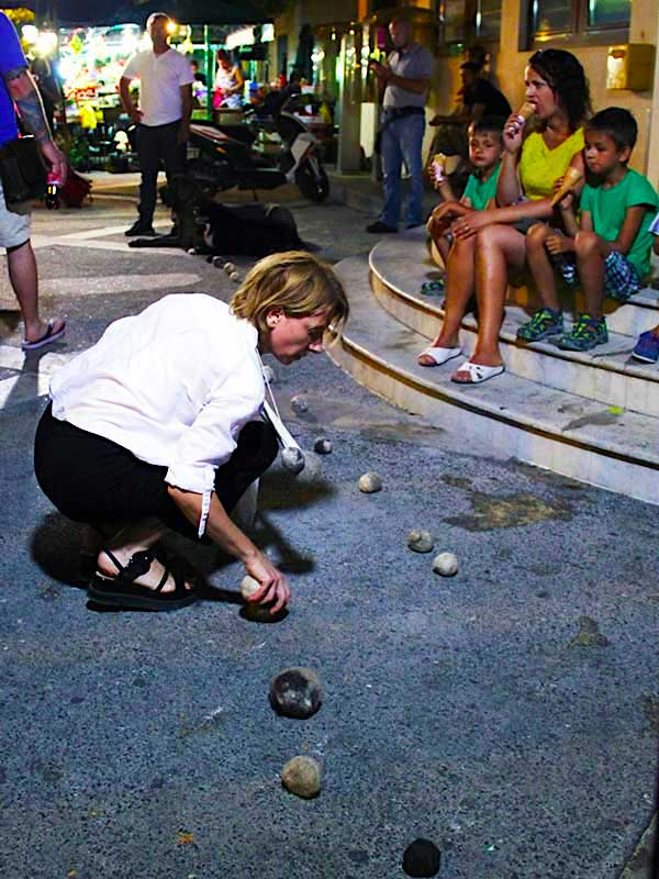woman placing dog hair balls on street in evening