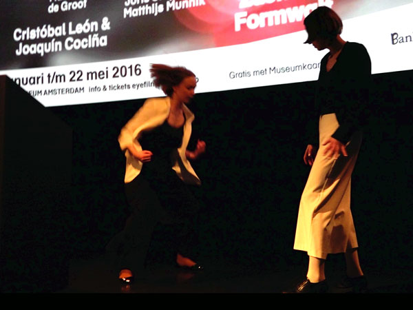 two women in black and white clothes dancing in front of cinema screen