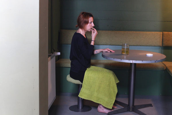 woman in black clothes eating pickles in green room