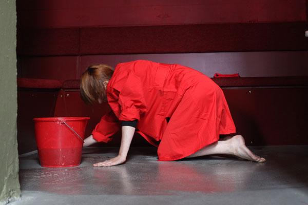 woman in red coat rubbing floor in red room