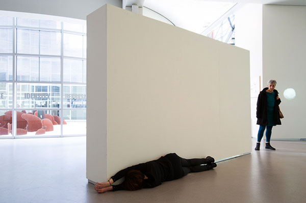 woman pressing body on white wall