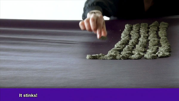 hand placing sand objects on purple sheet