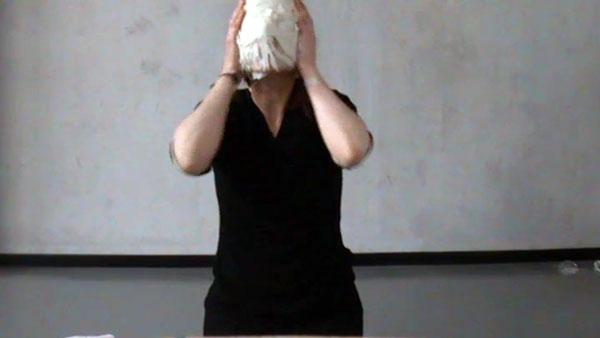 woman in black covering her face with pastry
